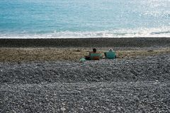 Two people relaxing on a pebble beach by the turquoise sea. Embankment of the famous French city of Nice. stock photo