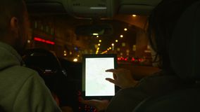 Two people riding in the car and discuss the route in tablet with map. Shoot with RED EPIC.  stock footage