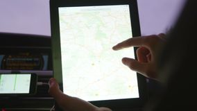 Two people riding in the car and discuss the route in tablet with map. Shoot with RED EPIC.  stock video footage