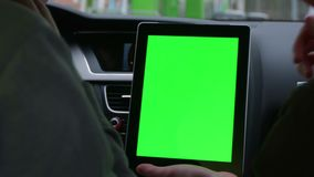 Two people riding in the modern car and discuss the route in tablet with green screen stock video