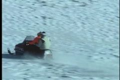Two people riding a snowmobile across ski slope stock video footage