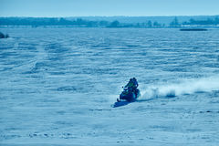 Two people riding on snowmobile on frozen lake. Two people riding on a snowmobile on the frozen lake Royalty Free Stock Photo
