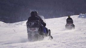 Two people riding snowmobiles through fresh snow on Mt stock video