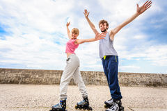 Two people on rollerblades with spread arms. Royalty Free Stock Image