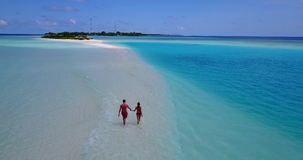V09054 Two 2 people romantic young people couple walking holding hands with drone aerial flying view on a tropical. Two 2 people romantic young people couple stock video