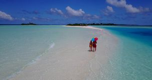 V09036 Two 2 people romantic young people couple walking holding hands with drone aerial flying view on a tropical. Two 2 people romantic young people couple stock video