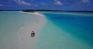 V09073 Two 2 people romantic young people couple walking holding hands with drone aerial flying view on a tropical. Two 2 people romantic young people couple stock video footage