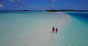 V09052 Two 2 people romantic young people couple walking holding hands with drone aerial flying view on a tropical. Two 2 people romantic young people couple stock video