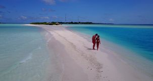 V09063 Two 2 people romantic young people couple walking holding hands with drone aerial flying view on a tropical stock video
