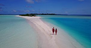 V09062 Two 2 people romantic young people couple walking holding hands with drone aerial flying view on a tropical. Two 2 people romantic young people couple stock footage