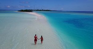 V09057 Two 2 people romantic young people couple walking holding hands with drone aerial flying view on a tropical. Two 2 people romantic young people couple stock video