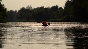 Two people rowing along the river with paddles sitting in a kayak are sent to sunset. Slow motion stock video footage