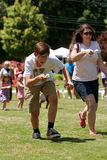 Two People Run In Egg and Spoon Race At Festival Stock Images