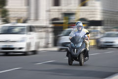 Two people on a scooter beverly three-wheel scooter (panning effect) Royalty Free Stock Image