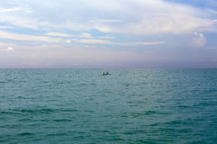 Two people in the sea in a rubber boat. Tropical turquoise blue sea. Royalty Free Stock Images