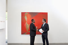 Two people shaking hands in front of wall painting Stock Photo