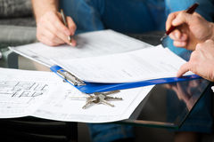 Two people signing a document Royalty Free Stock Photos