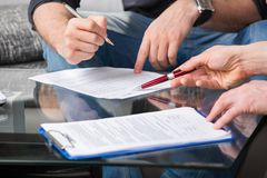 Two people signing a document royalty free stock images