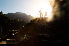 Two people in silhouette hiking at highland towards sunrise.  Lens flare intended.  Royalty Free Stock Photos
