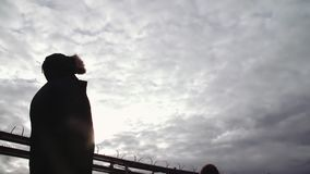 Two people silhouettes standing on river shore with highway bridge. Two people silhouettes in winter jackets standing on river shore with highway bridge on stock video