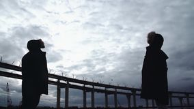 Two people silhouettes standing on river shore with highway bridge. Two people silhouettes in winter jackets standing on river shore with highway bridge on stock footage