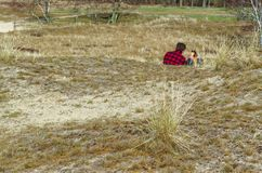 Two people sit on dry meadow on sunny day royalty free stock images