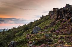 Two people sit on the rocks as the sunset lights the heather and rocks royalty free stock photo