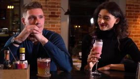 Two people sitting at the bar counter, woman sipping on a cocktail. Young woman sipping on a cocktail, looking and smiling at the man next to her stock video footage