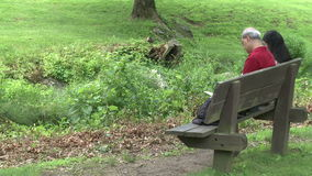 Two people sitting on a bench in a Nature Reserve (2 of 3). A view or scene of people stock video