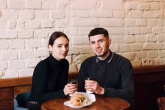 Two people sitting in a cafe, having breakfast, drinking coffe royalty free stock image