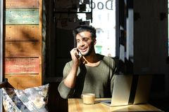 Lively conversation between two young people in cafe. Two people sitting in cafe by table near window. Modern laptop on table in front of man in dark sweater Royalty Free Stock Photography