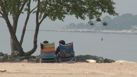 Two people sitting in folding chairs looking at the water. (1 of 2) stock video footage