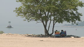 Two people sitting in folding chairs looking at the water. (2 of 2) stock video