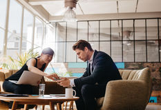 Two people sitting in office lobby using mobile phone. Shot of two people sitting in office lobby. Business partners working together in modern office looking at Royalty Free Stock Photography