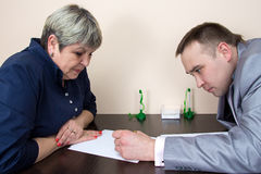 Two people sitting in office and writting Stock Images