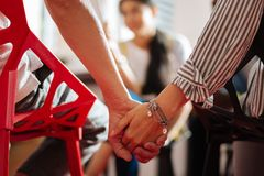 Two people sitting to together and holding hands during the psychological session stock photo