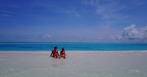 Two 2 people sitting together a romantic young couple on a tropical island of white sand beach and blue sky and. Sea stock video