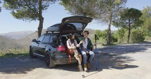 Two people sitting in trunk in mountains. Two young people with trekking poles sitting in car trunk and talking with mountains on background stock footage