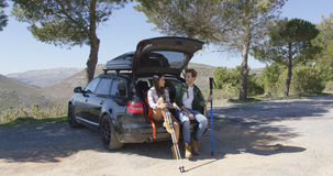 Two people sitting in trunk in mountains Royalty Free Stock Photography