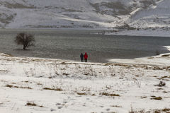 Two people in Snowy Landscape with Lake Royalty Free Stock Images
