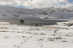 Two people in Snowy Landscape with Lake Stock Photography