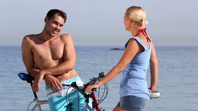 Two people speaking together on the beach. Two people speaking together and holding bike on the beach stock video