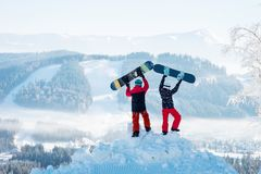 Two people stand with their backs on a snowdrift and raise their snowboards up. Against a white haze of snow-capped mountains and forests at winter ski resort stock photos