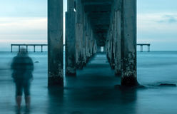 Two People Stand Under the Pier on a Cloudy Day Stock Images