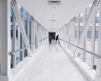 Two People Standing on Hallway Near Glass Window Royalty Free Stock Images