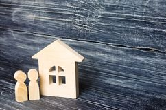 Two people are standing near the house. Wooden figures of person. S stand near a wooden house. The concept of a couple in love, cohabitants, parents, buyers and stock photography