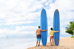 Two people standing with surfboars at beach. Two people young couple surfers standing with long blue surfboards on hawaii Kaanapali beach after surf class. Fun stock image
