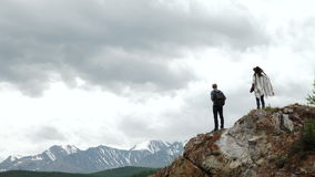 Two people standing on top of a mountain.  stock video
