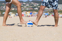 Two people stepping a ball on the beach Royalty Free Stock Images