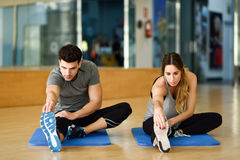 Two people streching their legs in gym. Stock Images